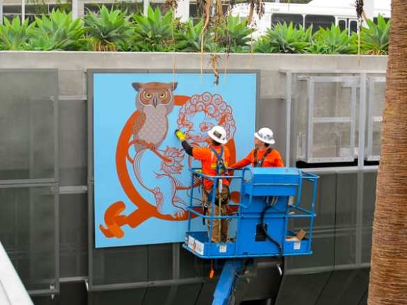 Phung Huynh's artwork being installed. Each artist created artwork in the medium of their choice, including drawing, painting and collage. This work was digitally captured in high-resolution digital files. The artwork was then translated onto 8' x 8' powder-coated aluminum panels, which can withstand the elements over the long-term, and are easy for Metro to maintain.