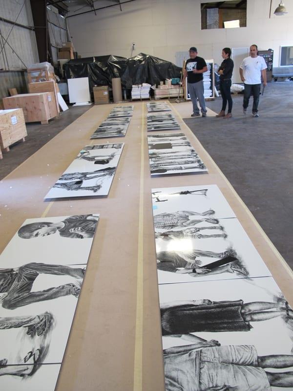 Abel Alejandre inspecting his artwork panels with Metro Art staff after they were delivered by artwork fabricator Winsor Fireform to ensure that his original artworks are accurately reflected, and that the black and white gradations are consistent among all twelve of the panels.