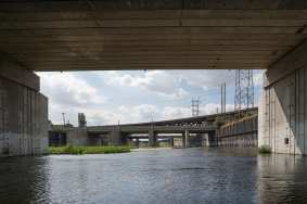A challenging section of the L.A. River just south of downtown with bridges and electric towers along the western bank.