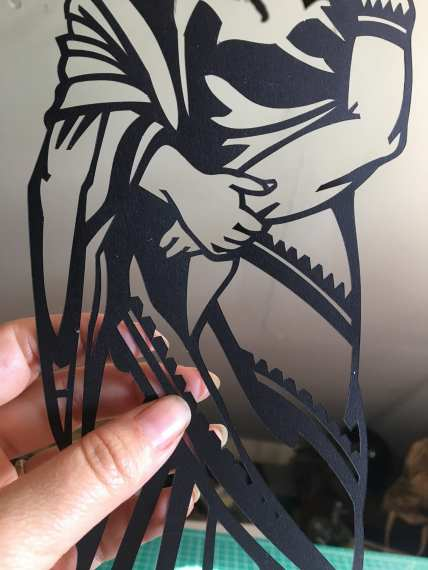 Romero holds a paper cut piece.