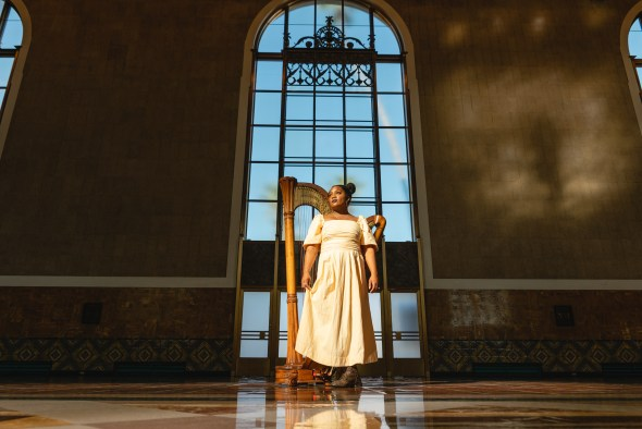 Woman stands in historic Union Station Ticketing Hall with a harp in and decorative arched window behind her