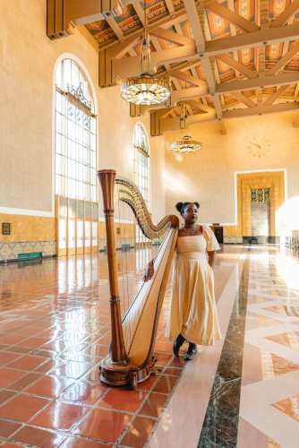Woman stands in historic Union Station Ticketing Hall with a harp in mid-morning sun