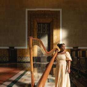 Woman stands in historic Union Station Ticketing Hall with a harp and light dancing behind her
