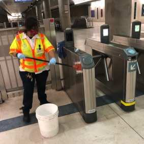 Metro staff cleaning and sanitizing turnstiles in preparation of reopening entrance.