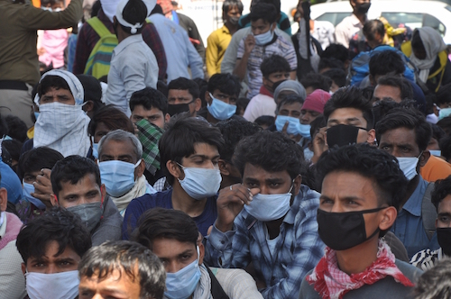 New Delhi: Scores of migrant workers heading back home seen at Anand Vihar bus terminal close to Delhi's border with Ghaziabad on Day 5 of the 21-day countrywide lockdown imposed to contain the spread of novel coronavirus, on March 29, 2020. (Photo: IANS)