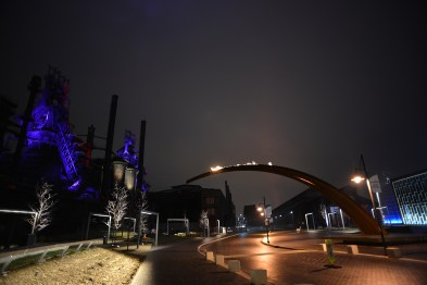 An archway leans across the main roadway on the site and has a flame that burns at night every hour, reminiscent of the furnace fires