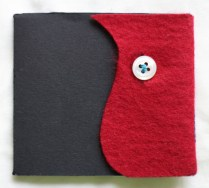 Concertina fold binding. Machine stitched to cover. Recycled felt and button.