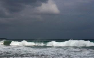 Dark sky, sunny day, blue sea.