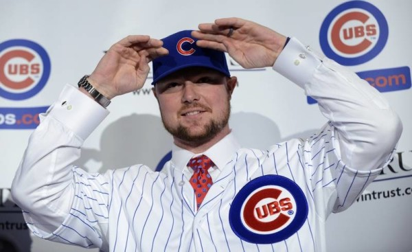 Pitcher Jon Lester models the cap and jersey of his new team Monday during his introductory news conference. Associated Press