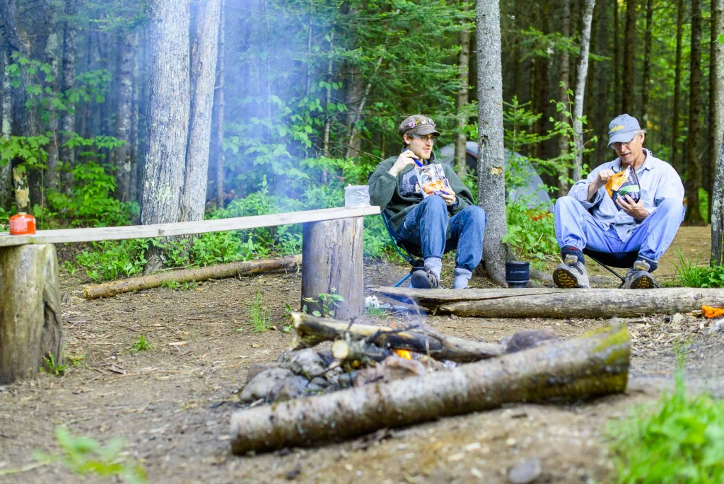 Father and son camping trip eating around fire