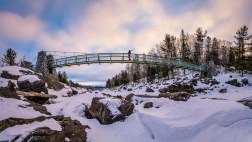 Crossing the Swinging Bridge in Jay Cooke State Park, Minnesota, on a frigid morning looking for sunrise and good skiing.