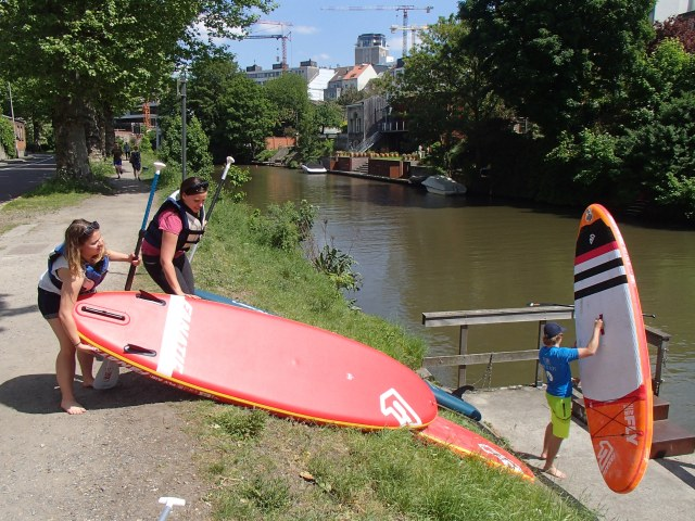 This image shows two girls going stand up paddleboarding in Ghent