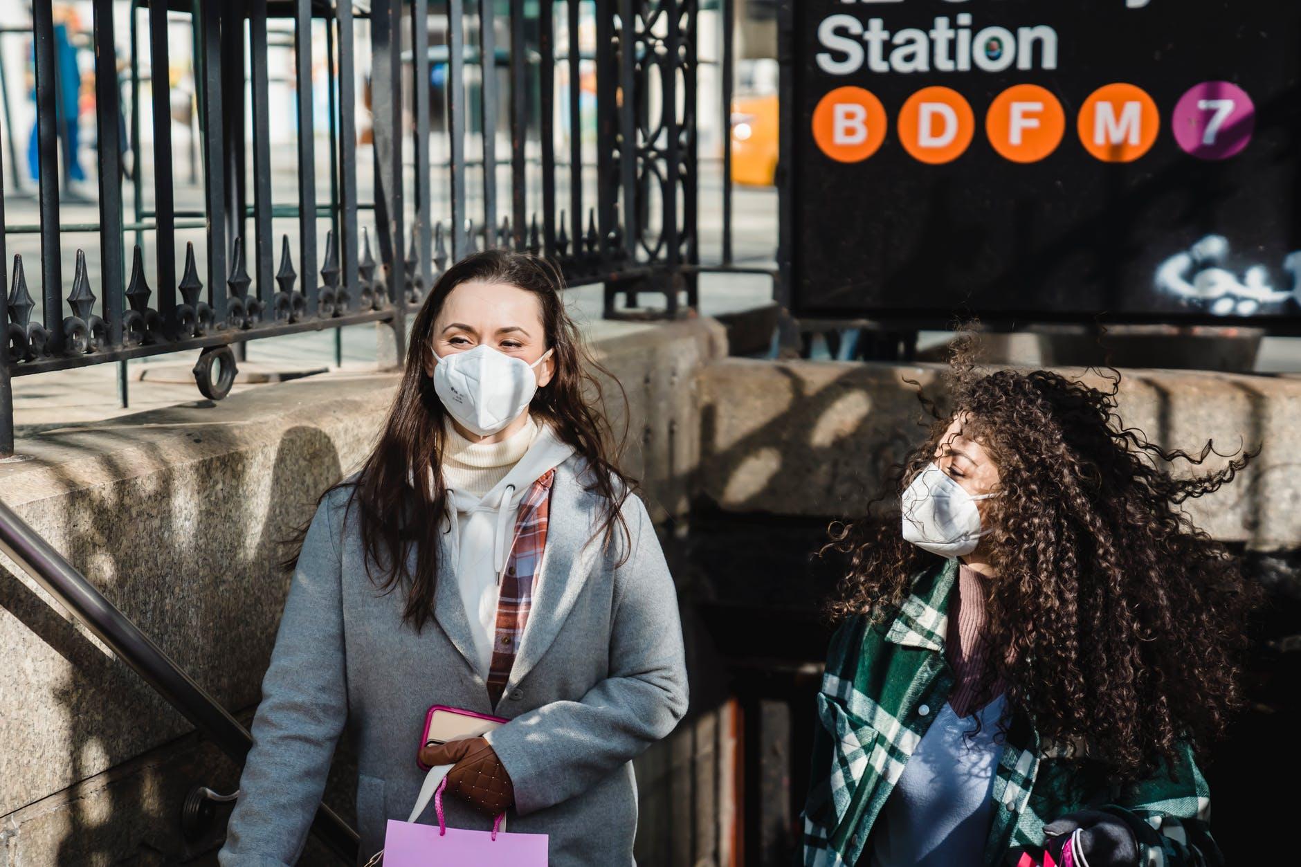 diverse women in medical masks walking out of metro