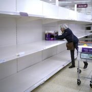 A senior citizen gets the last pack of toilet rolls at a Sainsbury