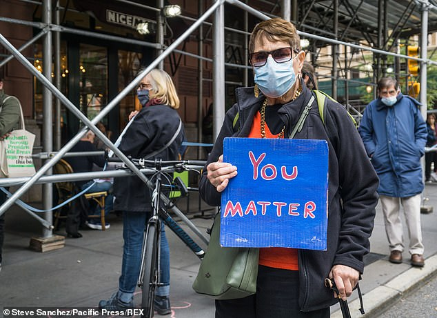A masked woman holds a sign telling homeless Lucerne residents: 'You matter'