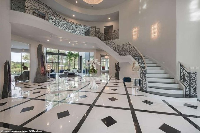 The entryway to the home is covered in pristine black and white marble surrounded by a sweeping staircase