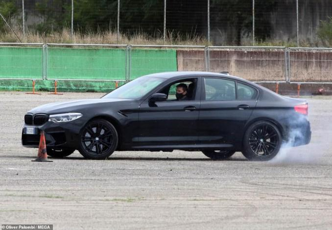 High-speed: Tom hopped into a sleek black sports car at one point during filming and looked in full control as he sped around cones