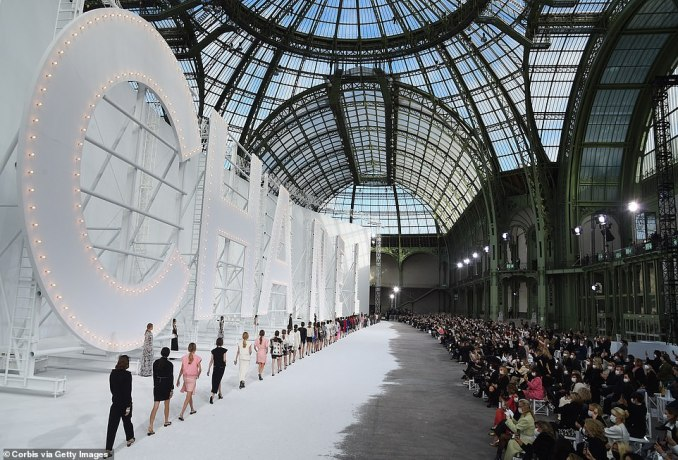 Guests, all wearing face coverings, perched on stools placed further apart than the shoulder-to-shoulder spacing typically seen on the front row of major fashion shows. Pictured, a view of the catwalk and guests at the Grand Palais