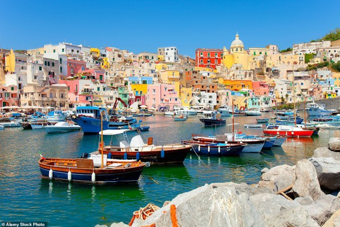The houses lining Procida, which is described as Italy's most colourful island, with houses a mix of pinks, blues, lilacs, yellows, greens and golds