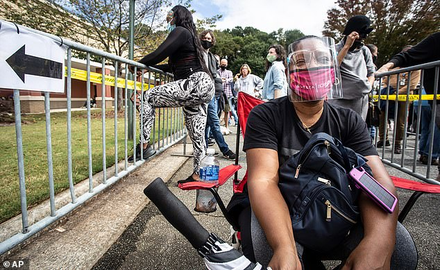 A woman wearing a face mask and shield sits as she waits in line for early voting on Monday in Marietta
