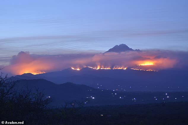 The fires burning on the slopes of Kilimanjaro at twilight, with flames visible a long distance from the mountain as the blaze enters a third day today