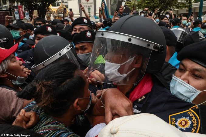 Clashes break out between Thai riot officers and demonstrators in downtown Bangkok during a second day of protests