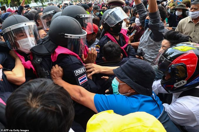 Pro-democracy protesters push back the police as they occupy part of downtown Bangkok