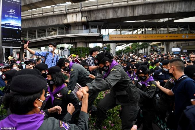 Police officers wade through the crowd as they attempt to regain control of downtown Bangkok