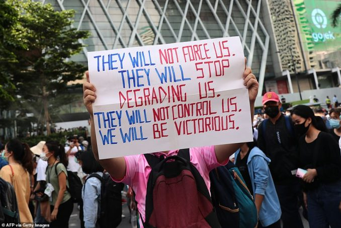 A pro-democracy protester holds up a banner during a rally in Bangkok