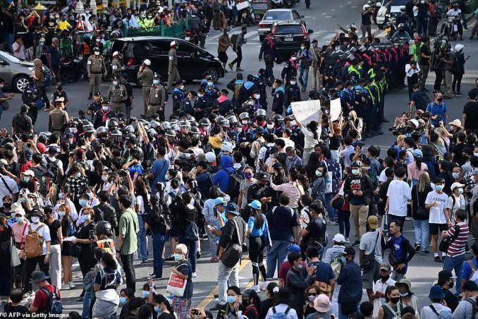 Pro-democracy protesters confront police during a rally on a traffic intersection in Bangkok