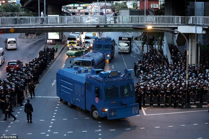 Hundreds of Thai riot police stand on either side of a Bangkok street as police water cannon trucks drive down the road ahead of protests on the 47th anniversary of the 1973 student uprising