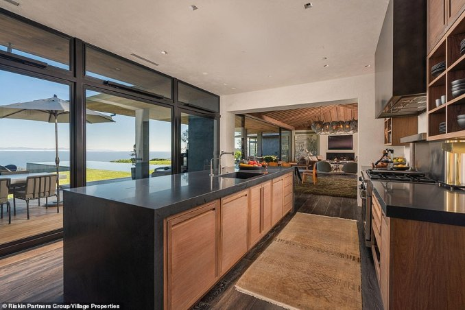 The open plan layout allows the kitchen to run on to more living spaces and the wooden deck patio for al fresco dining