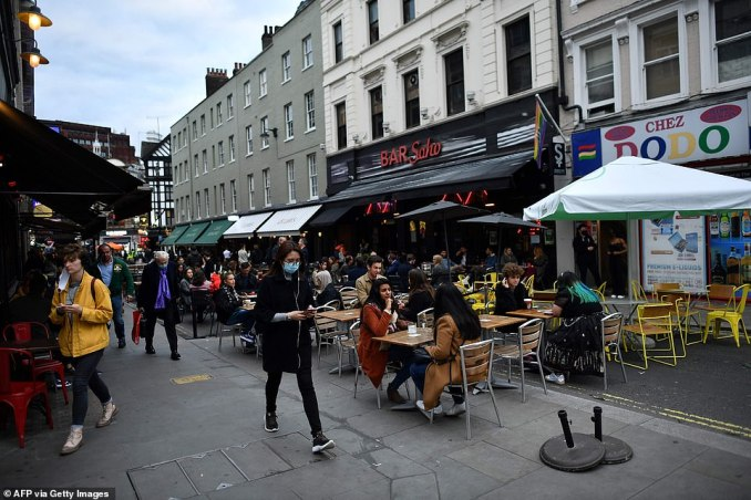 People enjoy their drinks outside at a bar in Soho despite chilly temperatures because of the latest coronavirus rules in the capital of the UK