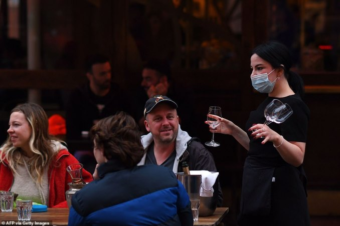 A barmaid hands out wine glasses as a group sits down outside a pub in Soho to enjoy a few drinks before the lockdown rules are worsened in London