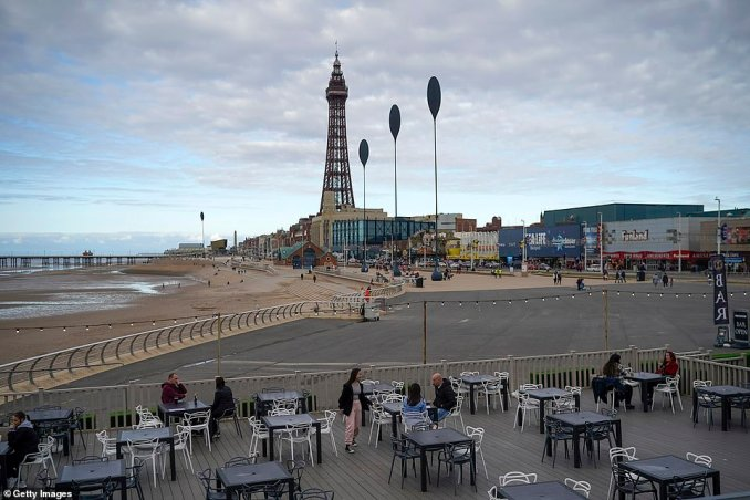 It comes as Lancashire heads into Tier 3 - meaning pubs and bars will be required to close with restaurants only allowed to serve customers who also order 'substanial' meals. The county has its last night of freedom before the rules are put in place at midnight. Pictured, people having a drink on the promenade in Blackpool this evening