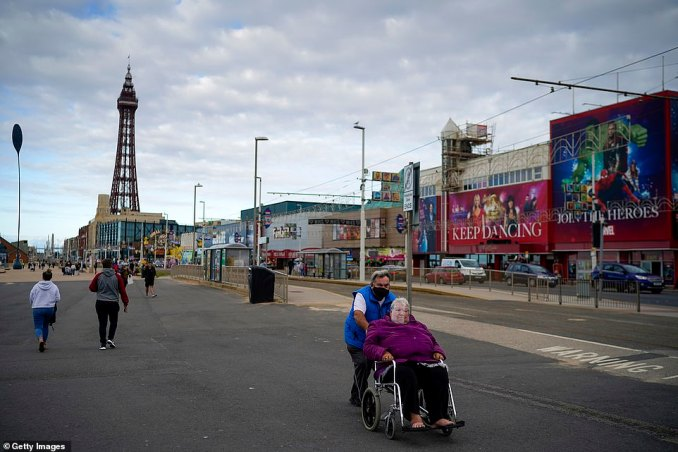 Pedestrians wear face masks and shields as they walk along the Blackpool promenade. Very few people appeared to visit the coastline amid rising coronavirus cases