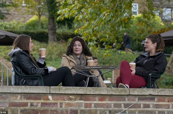 Small groups were seen heading out for coffee and keeping to social distancing guidelines. Pictured: Three friends sitting outdoors at a cafe in Richmond-upon-Thames