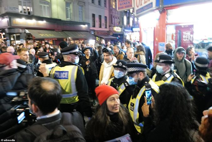 It comes after police fought to enforce coronavirus laws in London last night as they faced defiance from both protesters and drinkers refusing to go home. Pictured: crowds in Soho as pubs closed at 10pm