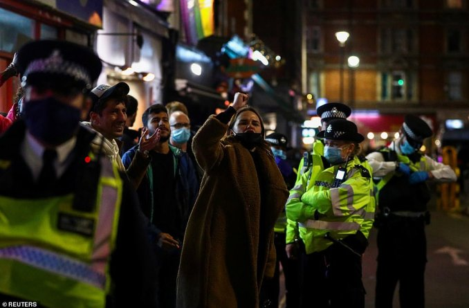 A woman appears to shout and raises her fist into the air while police officers stand waiting for the crowds to disperse in Soho on Friday night
