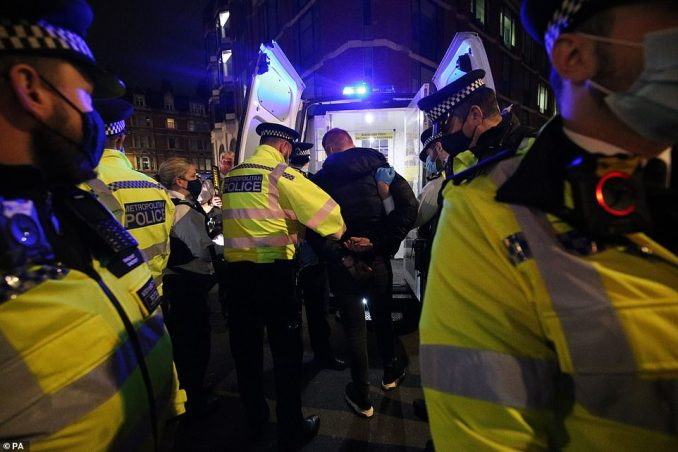 A man was put into the back of a police van after he was arrested and handcuffed as the pubs closed in Soho on Friday