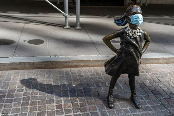 A face mask and a Ruth Bader Ginsburg collar is placed on The Fearless Girl statue during the Women's March outside the New York Stock Exchange