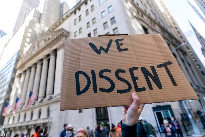 A protester holds up a sign that read 'We dissent' in front of the New York Stock Exchange on Wall Street on Saturday