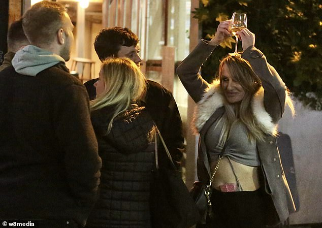 A woman held her drink over her head as she celebrated the night's fun. Pubs and bars closed at 10pm, prompting many to take to the streets to continue the party