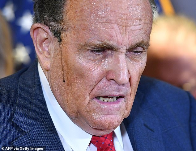 Running: The president's personal attorney Rudy Giuliani had matching streaks of either hair dye or make-up on both sides of his face as he addressed the media