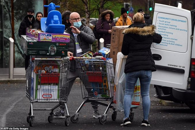 Shoppers leave a Smyths Toys shop with their purchases in Glasgow today ahead of the tough new restrictions