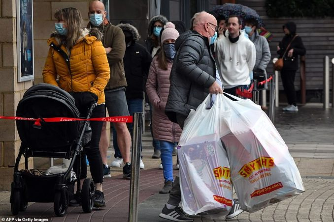 Shoppers queue to enter a Smyths Toys shop in Glasgow today while others leave with gifts