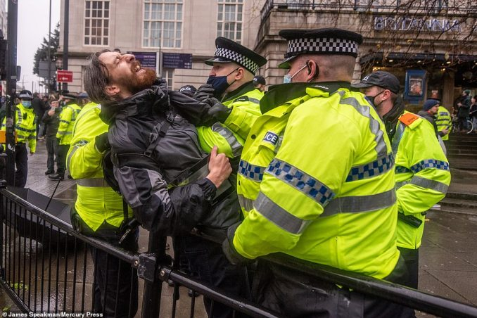 Police wearing face coverings restrain one of the protesters at the large rally in the rain through Liverpool city centre today