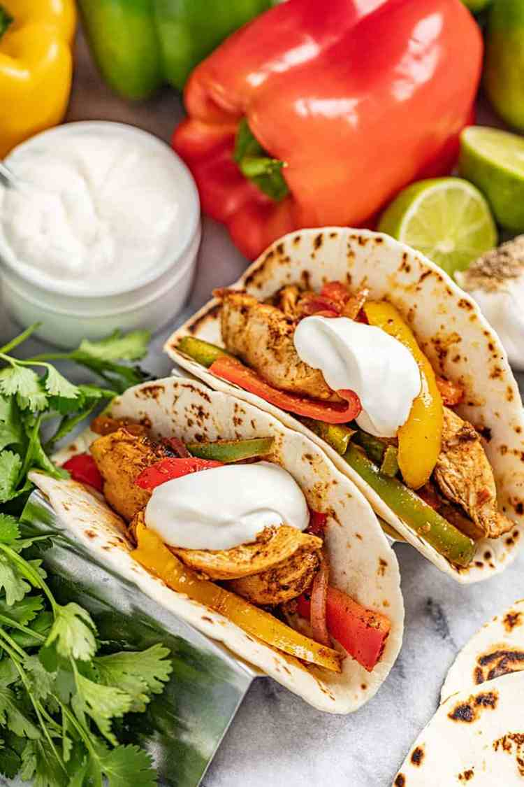 Chicken Fajitas in flour tortillas with multi colored bell peppers and onion