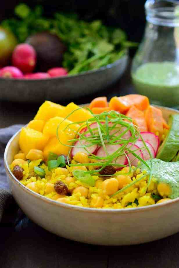 This vegan Buddha bowl is built on a base of fragrant curried rice and chickpeas and topped off with coconut-glazed sweet potato, fresh juicy mango, creamy avocado and a simple cilantro dressing. This curried rice vegan Buddha bowl is an explosion of flavours, simple to put together and a great make-ahead meal prep recipe.