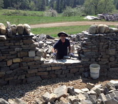 Section of dry stone workshop wall being rebuilt